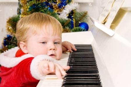 Boy dressed as Santa Claus near the white piano Stock Photo
