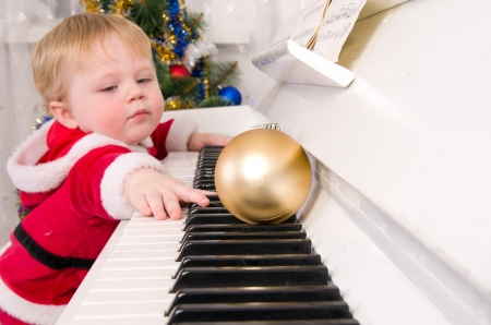 Boy dressed as Santa Claus near the white piano photo