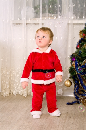 Boy dressed as Santa Claus in room photo