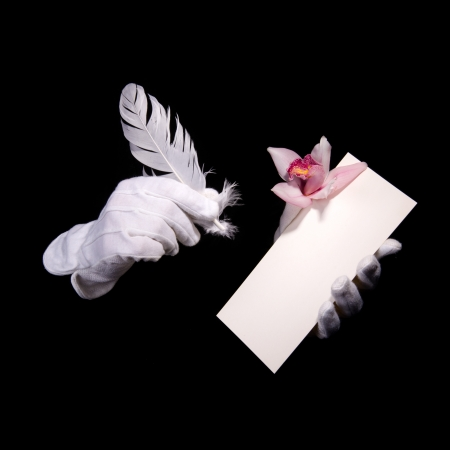 stilus: hands in white gloves on a black background holding a pen and blank