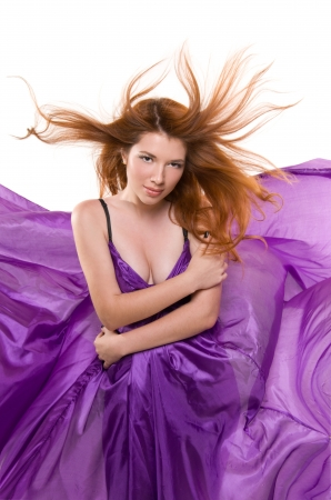 portrait of beautiful red-haired girl in a purple dress isolated on white background photo