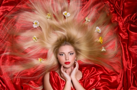 beautiful blonde with long hair lying on red satin fabric photo