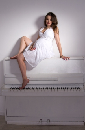 pregnant woman in room with white piano photo