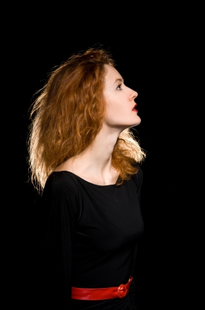 Portrait of red-haired girl on black background. studio set photo