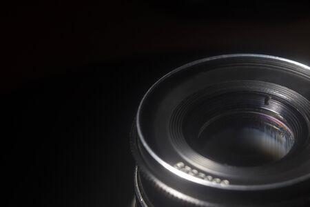 Old Soviet lens close-up on a black background in defocus 版權商用圖片