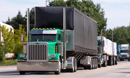 Big classic green rig ahead of a convoy of trucks