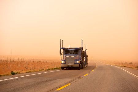 Big car hauler on the road in sandstorm, Arizona