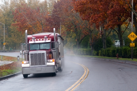 Big truck on the road in the rain on a background of autumn trees