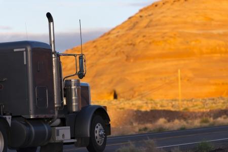 Dark classic semi truck passes by orange mountain
