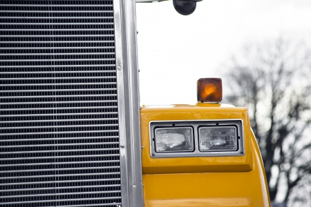 Detail of headlight and grille of yellow semi truck