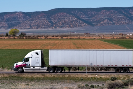 White big rig with crimson fenders and trailer at the field Stock Photo - 24873898