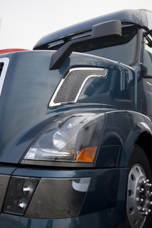 Dark blue semi truck in front side view with chrome details