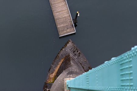 avant: Modern Top view of the green support and concrete foundation of the bridge, the dark water and the wooden pier with a restrictive column  avant-garde Stock Photo
