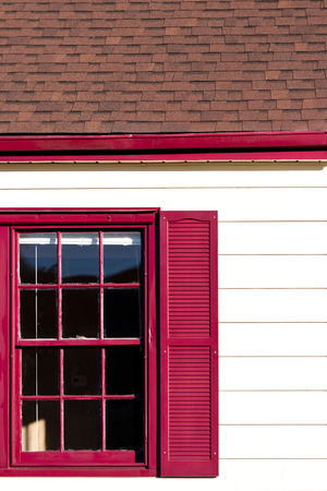 Red windon and gutters accent on the white siding and brown roof house  Stock Photo