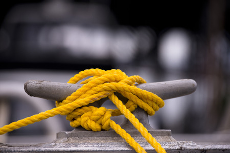 marine industry: Yellow mooring rope node on the grey metall hook and blurred black and white  Stock Photo