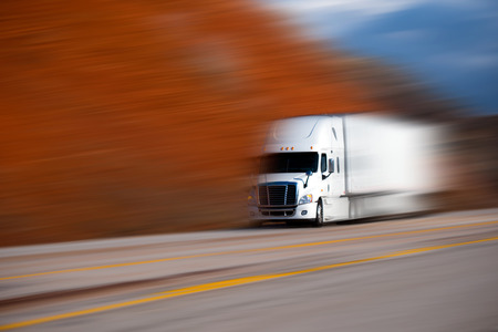 dividing lines: White big semi truck  and trailer on the road with yellow dividing lines on blurred colored