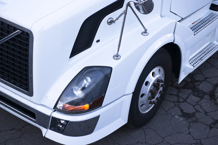 Detail of a white truck with a headlamp, wheel, mirror, bumper and grille photo