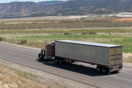 Big classic american semi truck with trailer on the road betveen fields Editorial