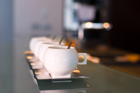 counter top: White porcelain modern cups with stainless steel saucers and spoons on glass counter top and blurred with light spots Stock Photo
