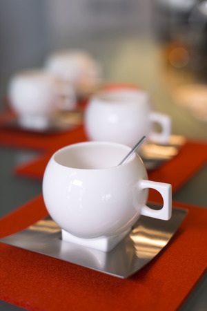 White porcelain modern cups with stainless steel saucers and spoons on glass counter top with orange coasters  photo