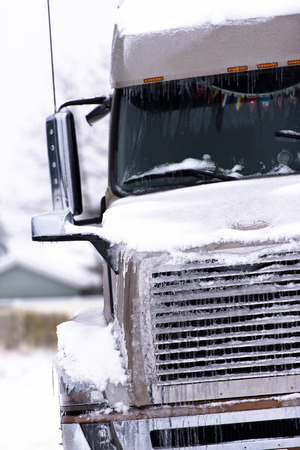 grille: Brown big modern semi truck with chrome grille and head lights in snow and ice Stock Photo