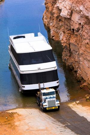 Big white classic semi truck take the bid contemporary boat from water of lake Powell, Arizona photo