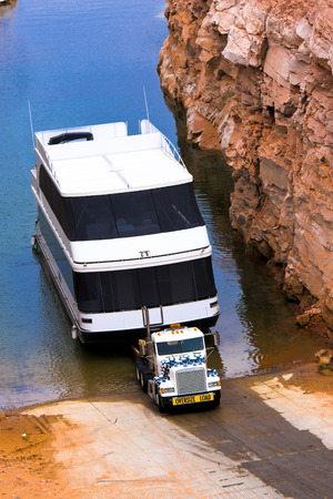 Big white classic semi truck take the bid contemporary boat from water of lake Powell, Arizona