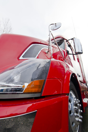 Bamper,wheel,mirror, headlight, body of bright red modern semi truck close view on light