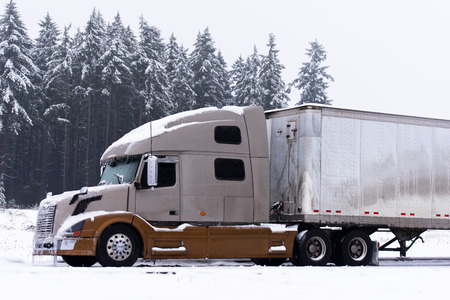 Brown and light brown colors semi truck and white trailer on winter road with snow and ice on winter snowed trees  Stock Photo