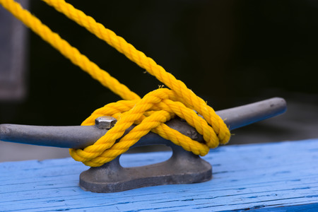 bolted: Yellow mooring nylon rope to the grey metal bracket,bolted to a wooden pier painted blue paint on dark  Stock Photo