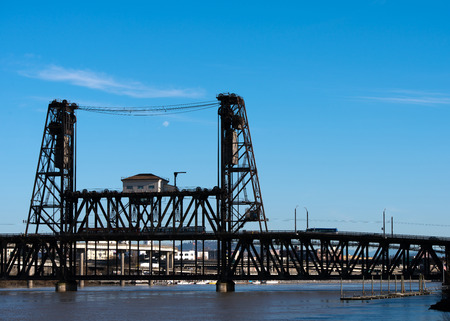 drawbridge: Classic old metal bridge truss lift with the lifting mechanism on the two towers over the River Willamette, Portland, Oregon on a background of blue sky with clouds