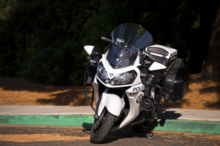 a white police motorcycle: Elegant modern white and black police motorcycle with recent findings gear standing on the road near the green border on a dark background of a large tree