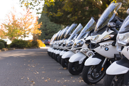 a white police motorcycle: Black and white police bikes in straight line on the autumn yard on green and yellow background