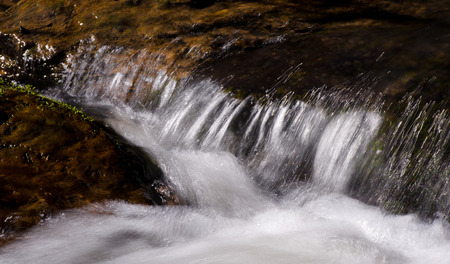 swiftly: Clear water of a mountain stream runs swiftly over the rocks ahead of time, and forms a thin white of a water thread