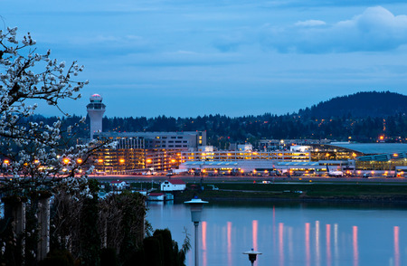 Evening Portland airport with lights reflecting in the water of the Columbia River, spring flowering tree in the foreground and hills covered with trees against the dark blue sky photo
