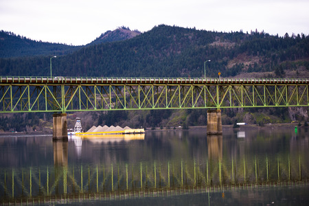Yellow laden barge, which pushes the lift, swims under green metal bridge across the river, which is reflected in the water on a background of mountains covered with green trees Stock Photo - 27478953