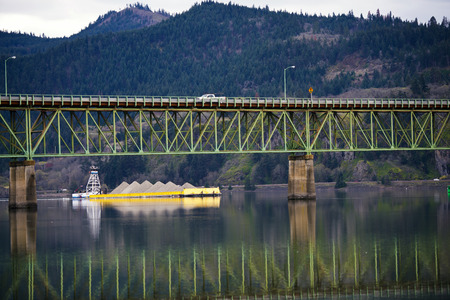 Yellow laden barge, which pushes the lift, swims under green metal road bridge across the river, which is reflected in the water Stock Photo - 27607430