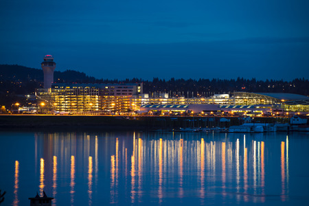 Evening view of the Portland airport with control tower, lights and reflection in the river, where boats are parked  In the lights parking of cars, aircraft, maintenance cars and trucks  photo