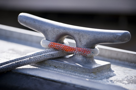 mooring: White flexible mooring rope with a red marking knotted on the metal bracket in silver color on the side of the boat Stock Photo