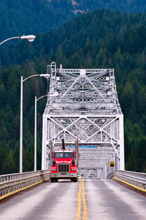 Red semi truck rides on the road with a yellow stripe dividing across the silver metal bridge photo
