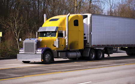 Yellow classic truck with trailer, purple wings, chrome pipes, chrome bumper and chrome visor on the road with yellow lanes  photo