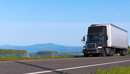 Dark modern semi-truck on the road along the river on a background of the islands with trees and mountains photo