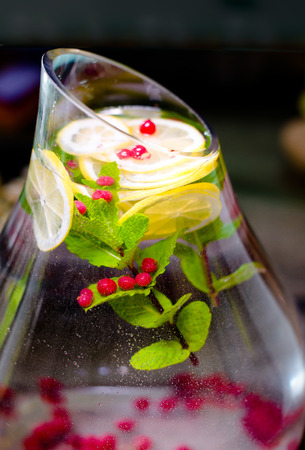 Healthy beauty modern fresh drink containing cranberry raspberry, mint leaves, lemon slices in Large Live with glass jug