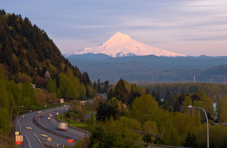 Curvy highway with moving cars passes through hilly terrain, overgrown with evergreen and deciduous trees on the background of snowy mountains, illuminated by the setting of the evening sun photo