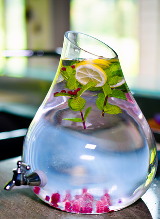 low cal: Appetizing refreshing healthy drink made from cranberries, mint, lemon slices, raspberries and water in a large glass container with crane