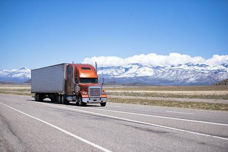 Grote oranje moderne klassieker mooie goed onderhouden semi vrachtwagen met twee rechte pijpen en witte koelwagen aanhanger op een snelweg tegen de achtergrond van de met sneeuw bedekte bergen en heldere blauwe hemel