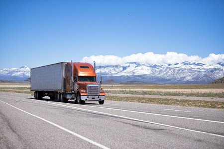 semi truck: Large orange modern classic beautiful well maintained semi truck with two straight pipes and white refrigerator trailer on a highway against the backdrop of snow-capped mountain ranges and clear blue sky