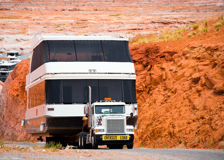 Large beautiful modern classic semi truck carries a huge vacation boat for a family on the trailer on the lake Powell on the background of bright orange rocks of Arizona Stock fotó