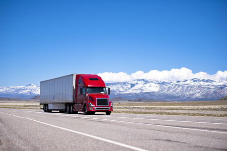 mountain ranges: Large beautiful modern classic-modern red truck with a high cab and trailer on a flat stretch of highway on a background of snow-capped mountain ranges, drowning in the clouds and clear blue sky