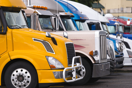 Modern yellow truck with aluminum wheels and aluminum bumper guard on the foreground a number of other trucks from different brands, colors, sizes and models of trucks at truck stop parking lot Stock Photo